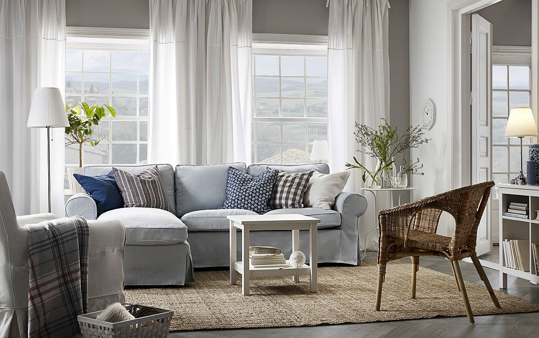 A Light Living Room Furnished With A Light Blue Two Seat Sofa With A Chaise  Lounge Filled With Cushions. Shown Together With A Small White Coffee Table  And ...