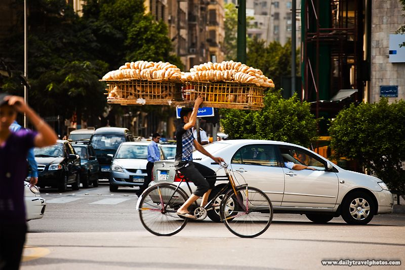A Bicycle Bread Delivery Guy Steadies A Rack Of Bread With One
