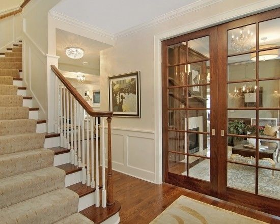 Traditional Entrance With Curved Carpeted Stairs And Woodenglass
