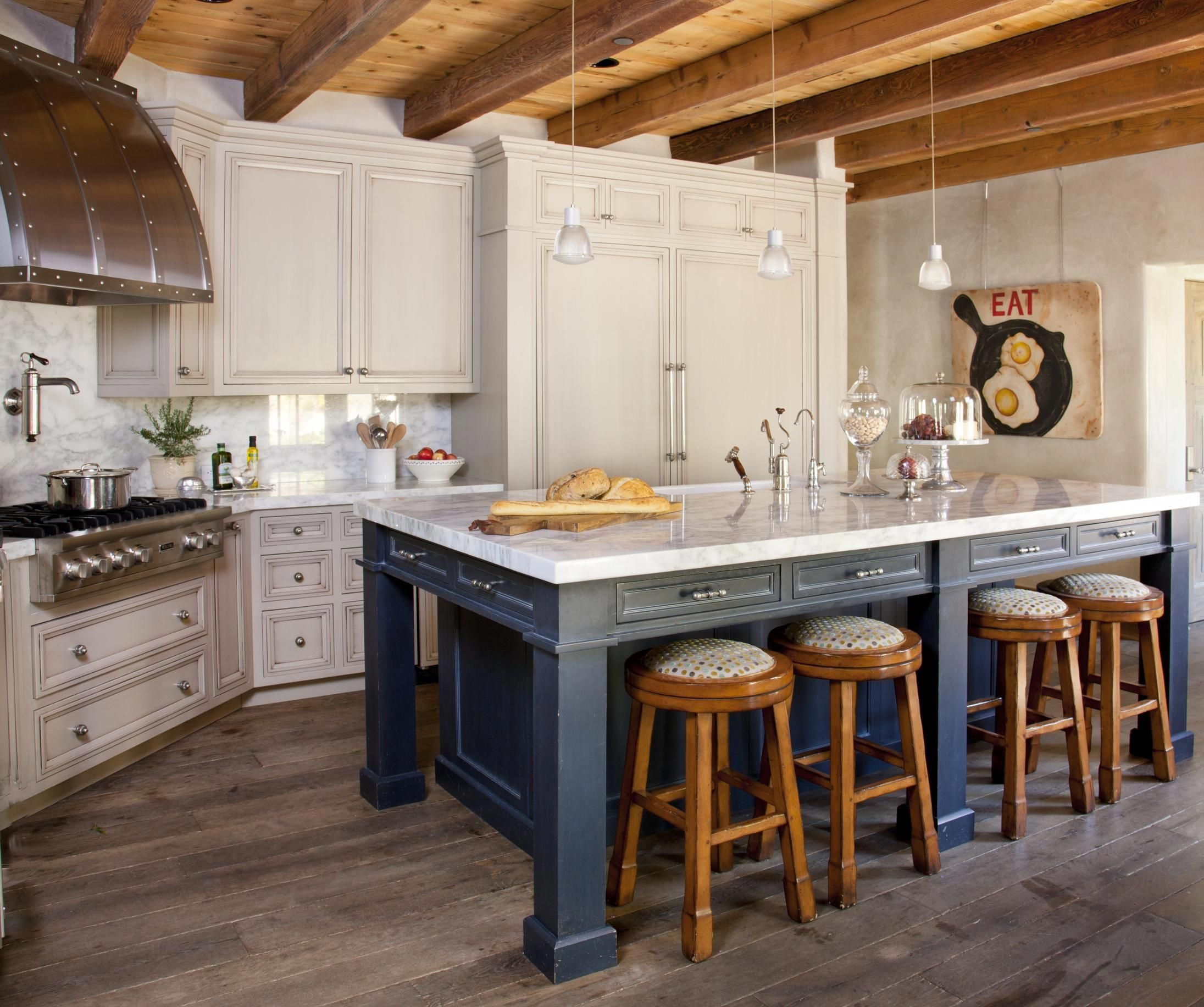 Antiqued kitchen cabinets and Calacatta marble countertops were