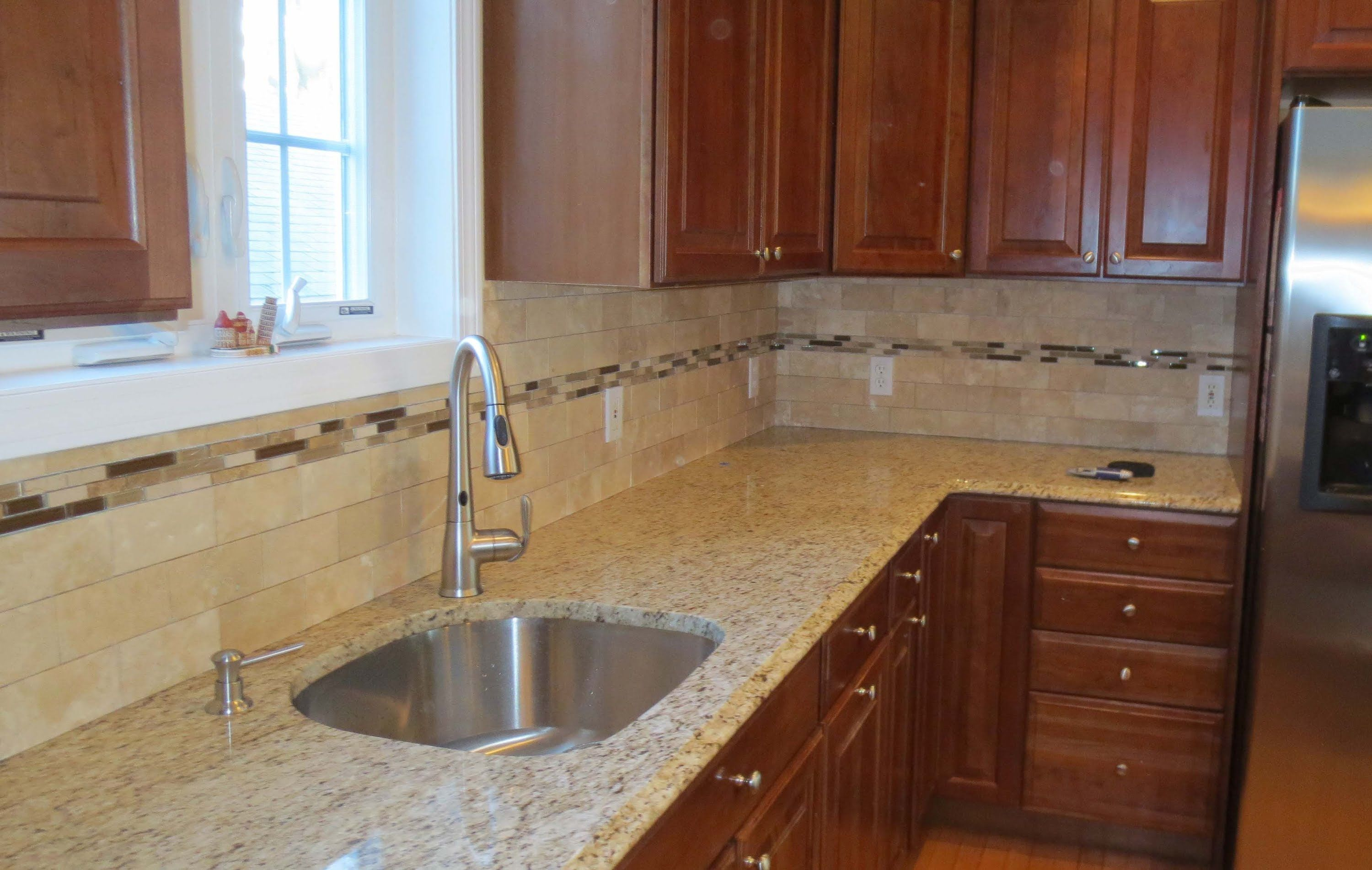 Travertine subway tile kitchen backsplash with a glass border