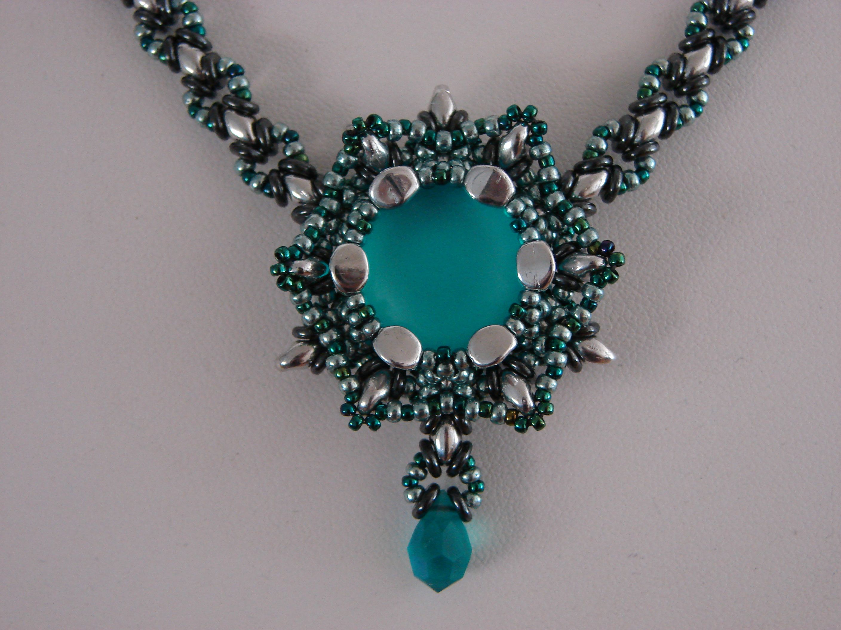 Beadwoven pendant and necklace. In the middle is a blue zircon lunasoft cabochon. Pinch beads, superduo's, 11/0 and 15/0 seed beads and O-beads are used in this piece. A pattern will be made for this one in time.
