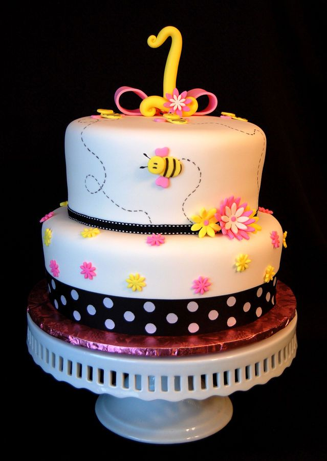Fondant covered bumble bee themed birthday cake, with black ribbon and pink and yellow daisies.