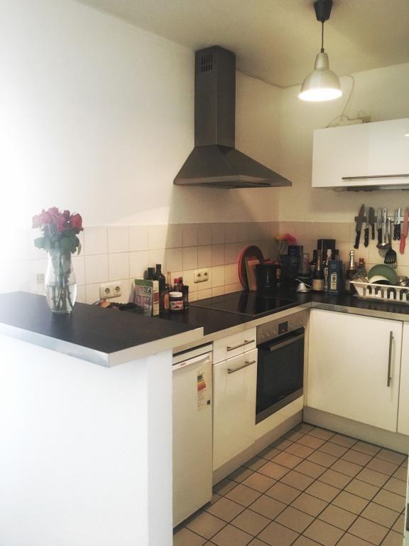 Schöne helle Küche mit dunkler Arbeitsplatte und Dampfabzugshaube ...