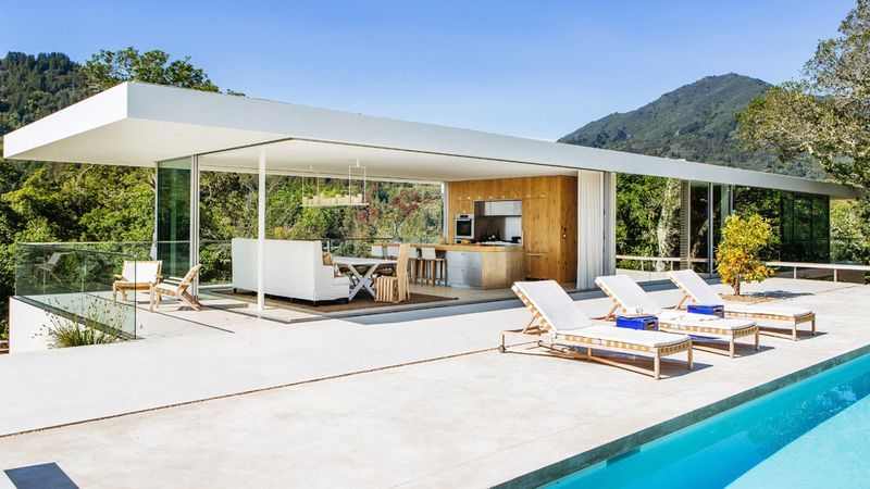 Conceived as a plinth and a pavilion, the home features bedrooms on the lower level and a completely indoor-outdoor dining and living pavilion that opens up onto the deck and swimming pool.