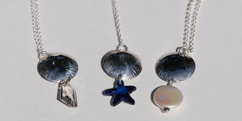 Chased dome pendant with Swarovski de-art crystal. $90