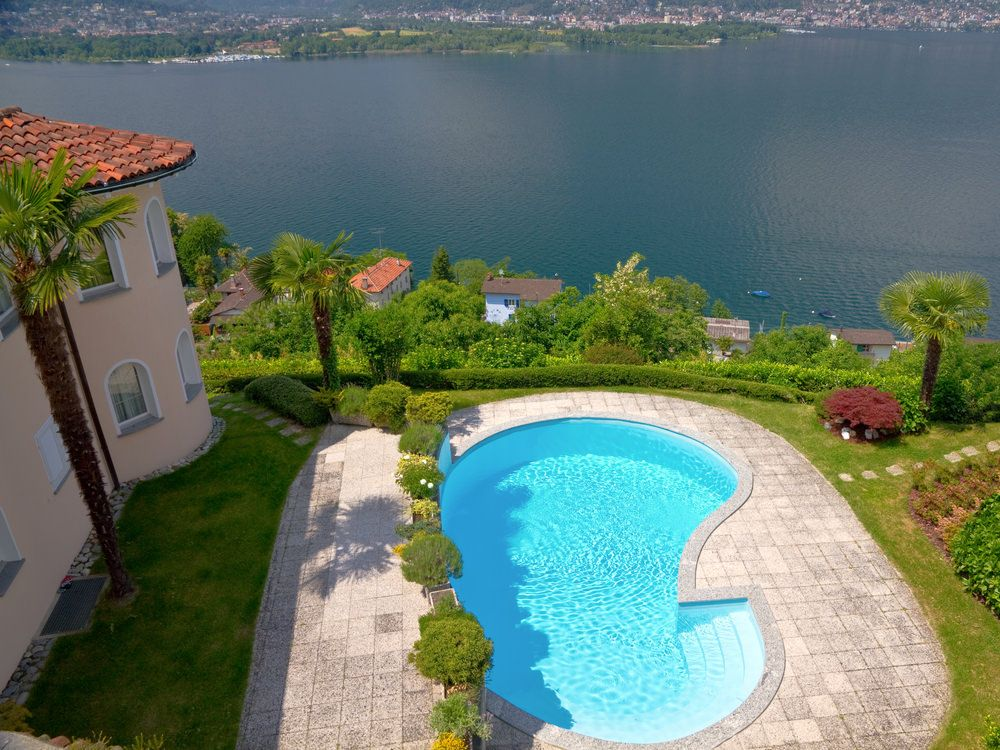 I love aerial pictures of landscaping. This is a spectacular view of a light blue kidney-shaped pool with patio overlooking the lake.