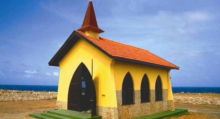 With buttery yellow walls, cocoa brown wooden doors and an orange roof - Alta Vista Chapel in Aruba