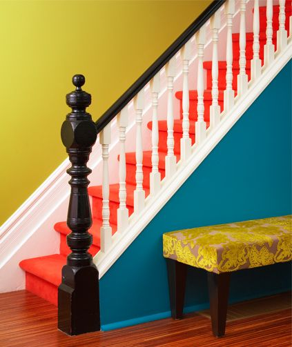 Bright orange stairs with blue and yellow walls.  I love it!