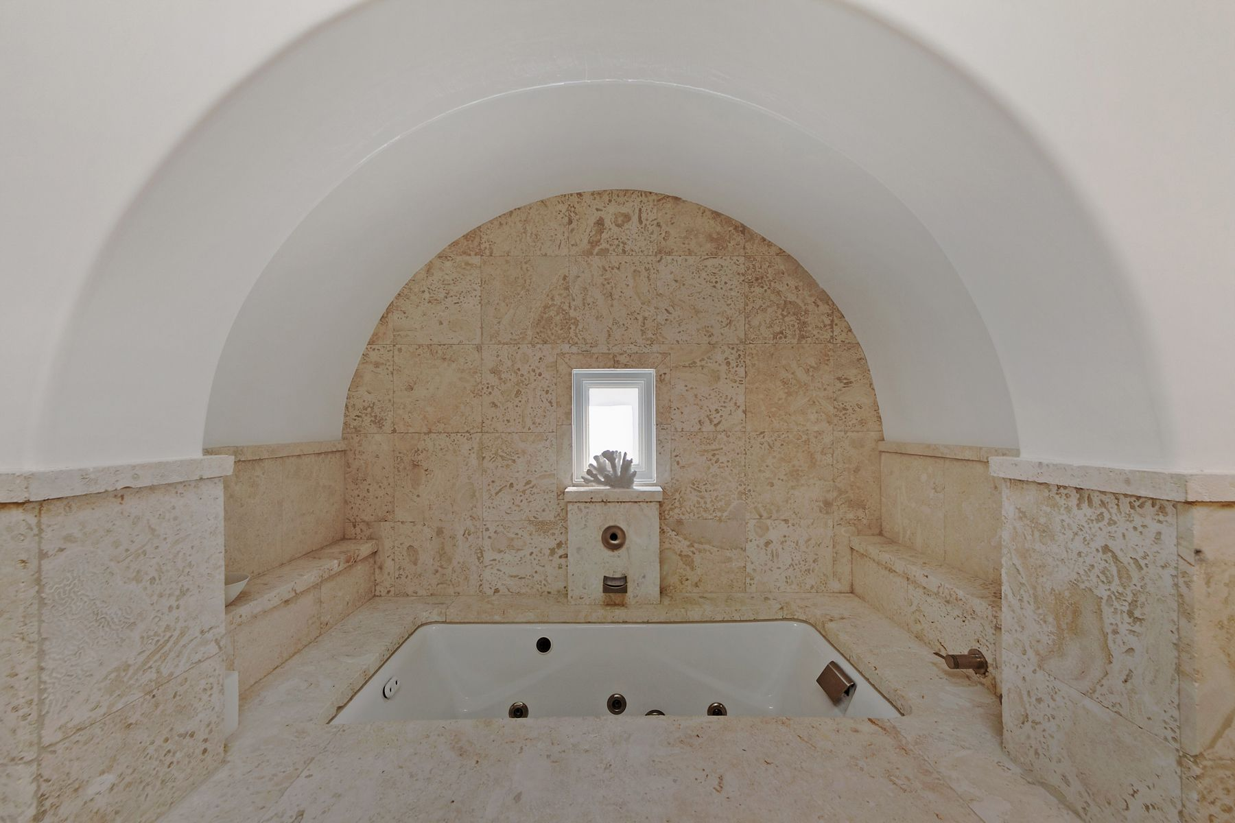 Rounded Venetian plaster and shell stone walls surround a jetted tub ...