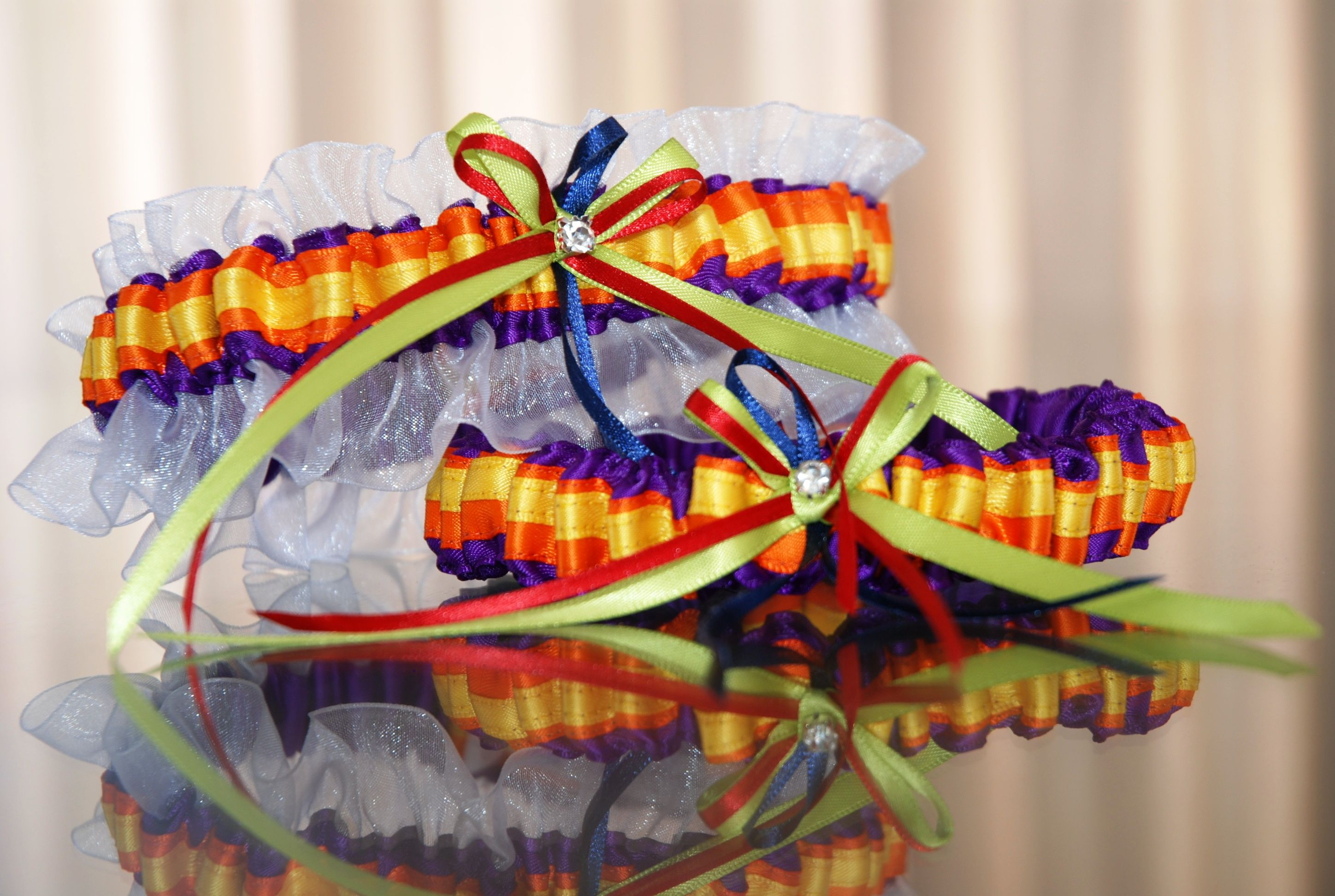 Main garter:  White organza with purple, orange, yellow satin with red blue and green bows. Tossing garter: Purple, orange and yellow lace with red, blue and green bows. louise@heavenlygarters.co.za