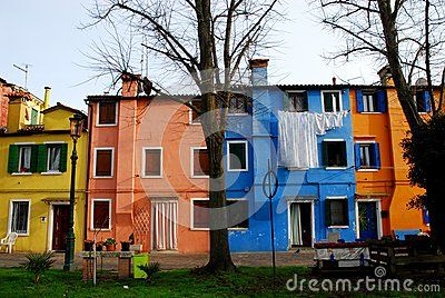 Photo made in the island of Burano in Venice in Italy. In the image you see in the foreground a meadow and two tree trunks, in addition you can see the colorful facades with very intense colors of some houses, narrow to each other, overlooking a small courtyard. Front of the house blue there are white sheets to dry.