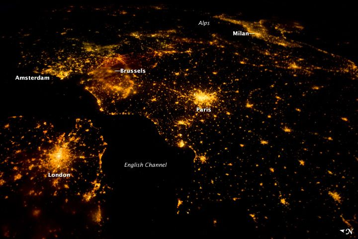 """Several of the oldest cities of northwestern Europe are highlighted in this astronaut photograph from just after midnight (00:25 Greenwich Mean Time) on August 10, 2011. While the landscape is dotted with clusters of lights from individual urban areas, the metropolitan areas of London, Paris, Brussels, and Amsterdam stand out due to their large light """"footprints."""" The metropolitan area of Milan is also visible at image upper right. While each of these cities is, or has been, the capital of a…"""