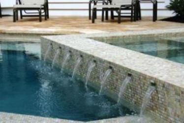 As water cascades from the wall each glass tile sparkles for Swimming pool wall tiles