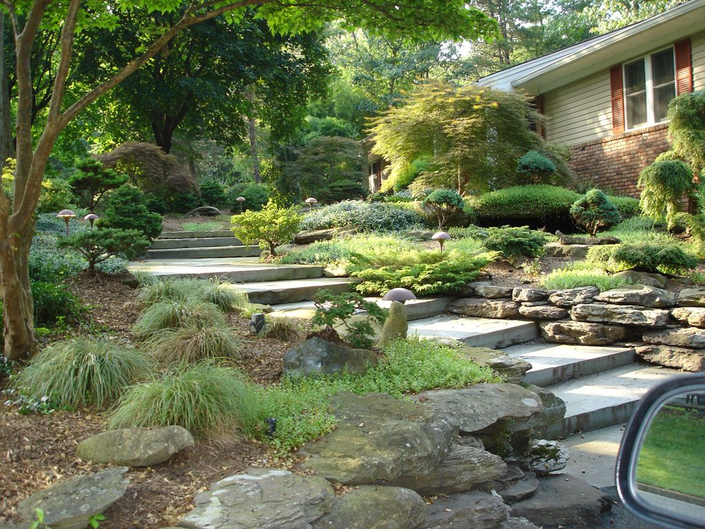 The natural stone steps of a stairway garden feature climb a small - Front Of House Landscaping With Natural Stone Staircase In Upper Saddle River Bergen County
