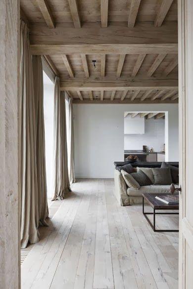 Dans ce grand salon aux murs gris perle et au style épuré la couleur lin des rideaux se cale ton sur ton avec la couleur du plafond plancher