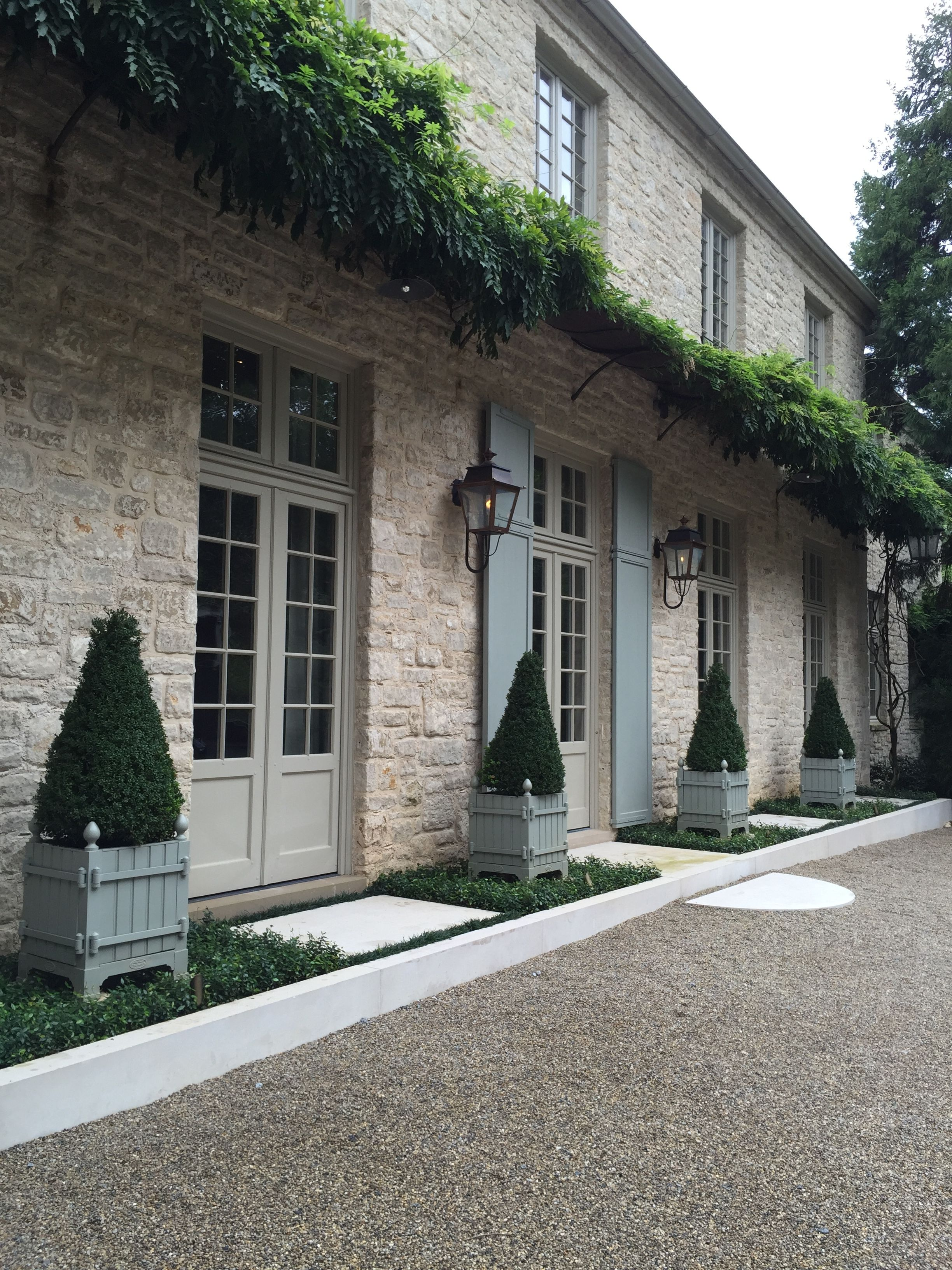 Motor court entry with Versailles Tubs planted with topiary Boxwood.