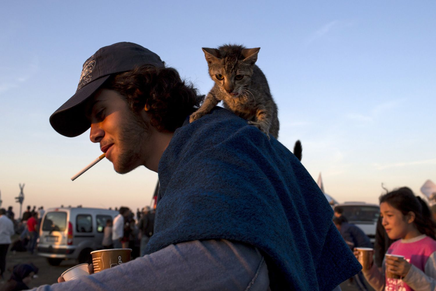 Omer, from Syria, carries his cat, Johnny, on his shoulders at a collection point for migrants in the village of Roszke, Hungary