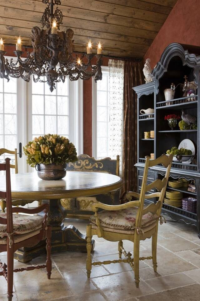 French Country Dining Room With Open Hutch Full Of Ceramics A Chandelier And Homey Rustic Vibe