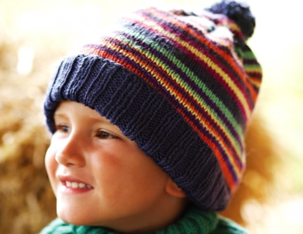 Warm, bequem und keck sieht diese Ringelmütze mit Bommel aus, die von kleinen Jungs und Mädels sicher gern getragen wird. Mit Bündchen und Streifen.