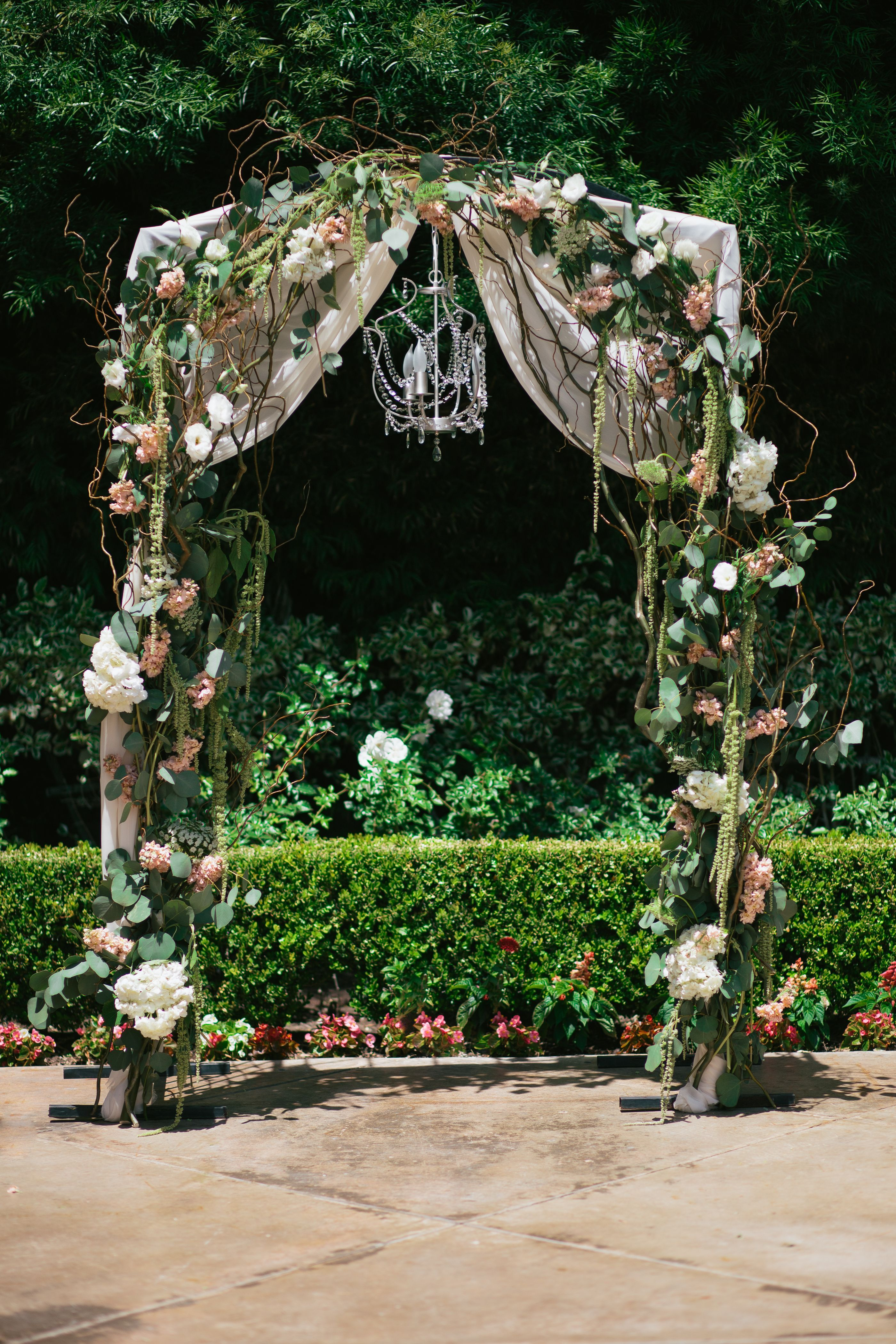 Wedding Arch With Chiffon Draping And Chandelier For Added Touches