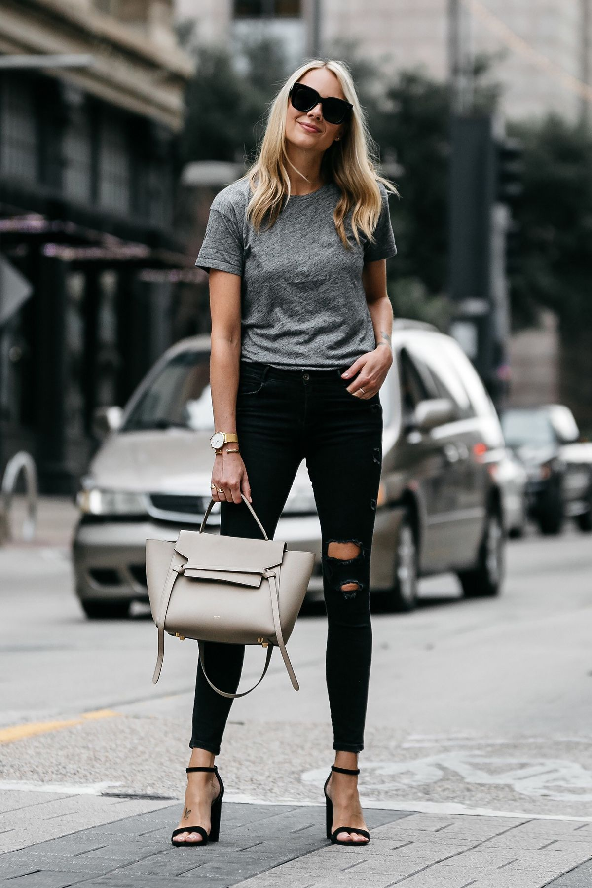 b7701c48d5 Blonde woman wearing Madewell grey tshirt zara black ripped skinny jeans  outfit steve madden black ankle strap heels celine belt bag street style  dallas ...