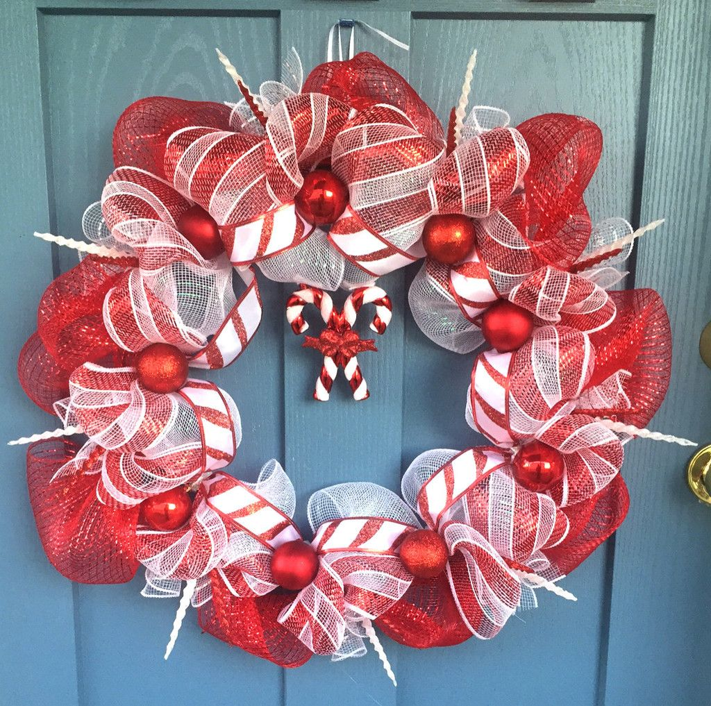 Wire wreath frame covered with red and white mesh intertwined with ...