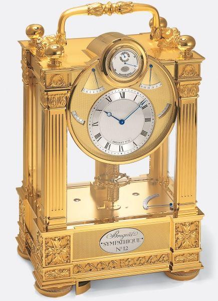 """Reloj de sobremesa """"Sympathique"""" con reloj de pulsera dependiente construido según los principios establecidos por A.-L. Breguet en 1793. El reloj de pulsera se ajusta y carga diariamente de manera automática al ser colocado en el hueco de la parte superior del reloj principal. Marco de bronce dorado. Movimiento con escape de cronómetro de fuerza constante. Indicación del día, mes, fecha, edad y fases de la luna y ecuación de tiempo. Termómetro Celsius."""