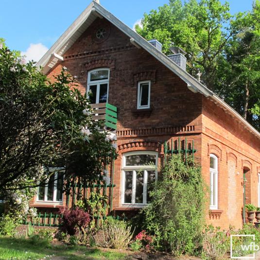 Dieses idyllische Landhaus im Grünen hat klassiche weiße Holzfenster ...