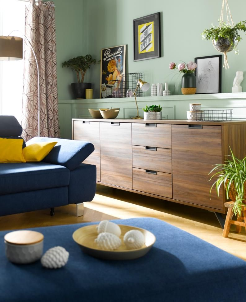 Wer sich eine Polsterecke in einer starken Farbe wie azurblau wünscht, hat mit dunklen Holztönen, leicht gemusterten Vorhängen und natürlichen Dekoelementen alle Möglichkeiten, ein harmonisches Gesamtbild zu gestalten.
