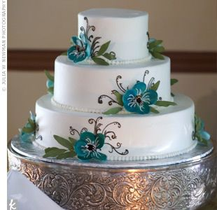 Because Ken is a pastry chef, the cake had to be impressive. The three-tiered confection featured dark chocolate with bananas, caramel mousse, and buttercream frosting. The outside reflected the design from the invitations and stationery -- blue flowers w...