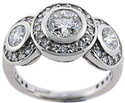 Bezel & Pave Settings Used Together: This diamond ring features three bezel set diamonds as focal points. Each of the three stones are surrounded by round, pave set diamonds that give the design a floral-like appearance. The combo illustrates just one possibility when setting types are combined.