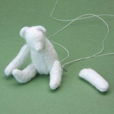 Executando uma agulha na diagonal para cima através do corpo de um urso polar em miniatura para adicionar braços articulados.