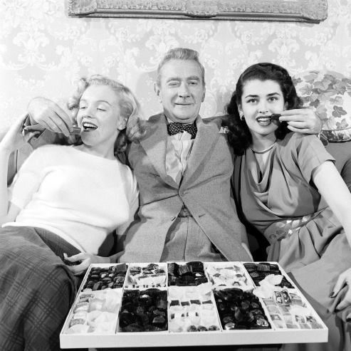 """A rare press shot featuring star Clifton Webb supplying chocolates to an unknown """"Marilyn Monroe"""" and cult star Laurette Luez to help promote the 1948 FOX comedy classic, SITTING PRETTY!"""