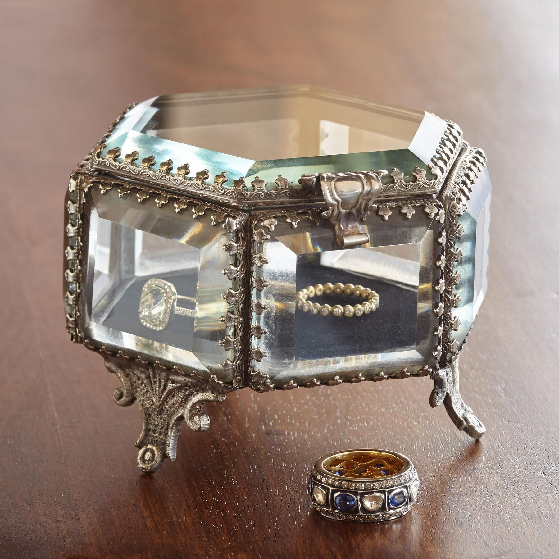 "HEXAGON JEWELRY BOX -- Beveled glass trimmed with ornate brass sits atop gracefully scrolled legs, turning jewelry into a dressing table display. Lined with velvet, it's a handcrafted ode to a bygone era of glamor. 4""W x 4""D x 2-3/4""H."