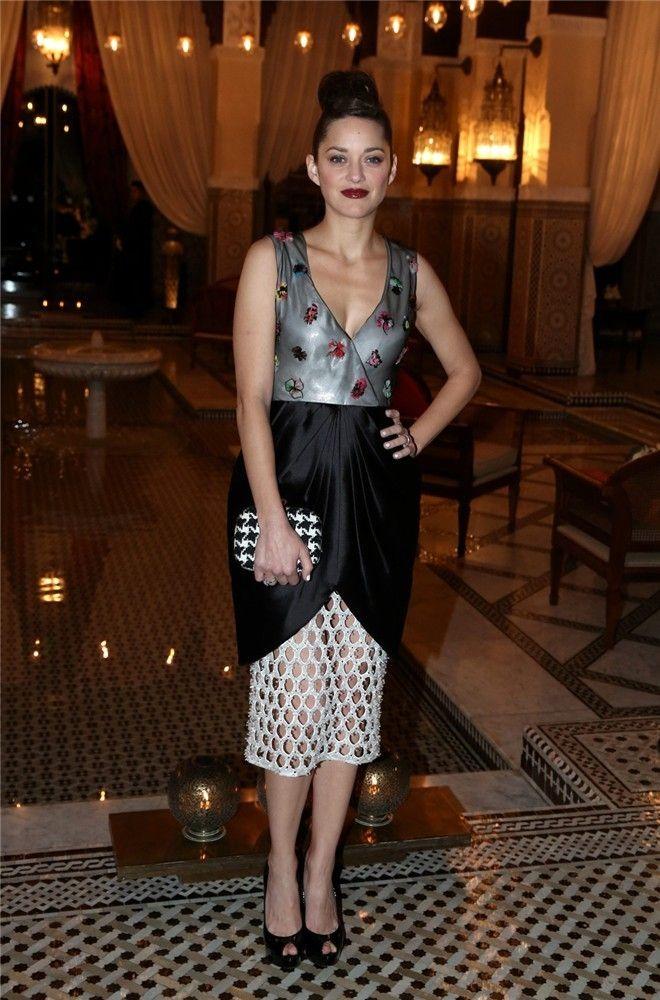 Marion Cotillard deslumbra en la Fiesta Dior de Marrakech. La bella actriz francesa optó por un vestido de Dior, en color gris, negro y blanco. Completaba su look con un elegante moño alto, sin joyas, y una original cartera.