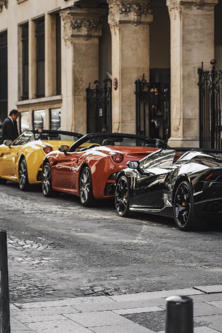 some expensive luxury cars in the middle of Paris. / black Lamborghini