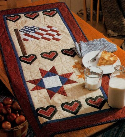 Americana Summer Quilted Table Runner Pattern is part of Table runner pattern, Quilted table runners patterns, Table topper patterns, Summer quilts, Flag quilt, Patriotic quilts - Hearts, bars, and stars adorn this charming patriotic quilted piece  Download the Americana Summer Quilted Table Runner Pattern and find instructions on how to make it in this helpful article