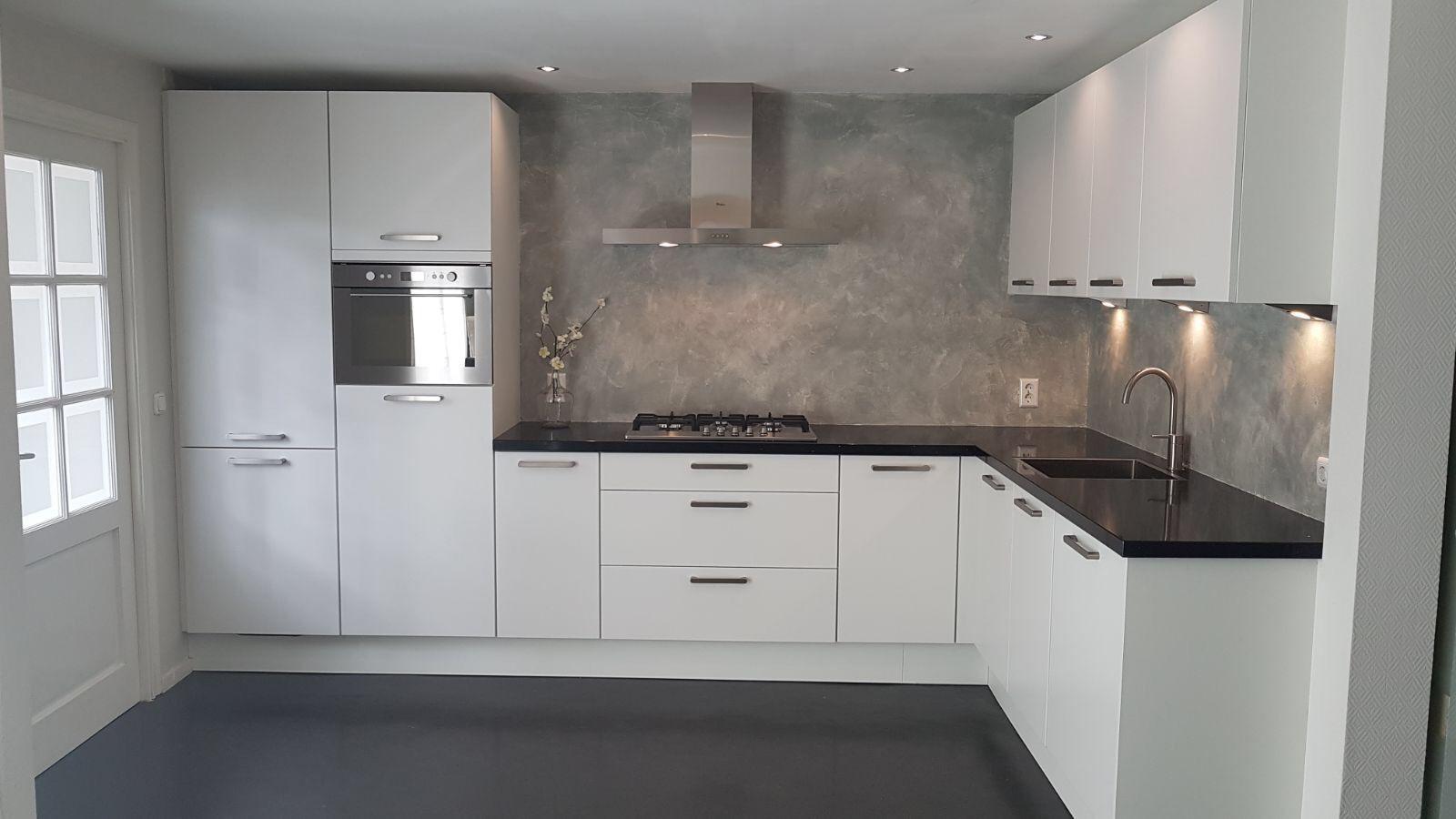 Zwart witte keuken met betonlook achterwand en keukenblad van