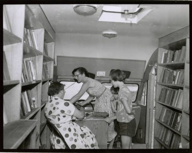 Johnston County bookmobile, girls looking on as librarians work, 1955  ^cs