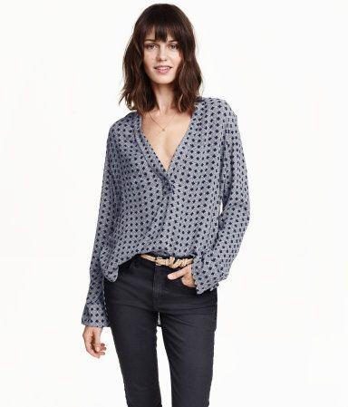Weite V-Bluse aus Crinkle-Stoff mit Musterdruck. Lange Ärmel mit geschlitzter Manschette. Seitliche Schlitze am Saum und etwas verlängertes Rückenteil.