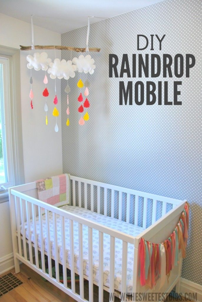 a DIY raindrop mobile made from felt and hung with a driftwood stick. Easy tutorial and looks so sweet in this little girl's nursery! - via the sweetest digs