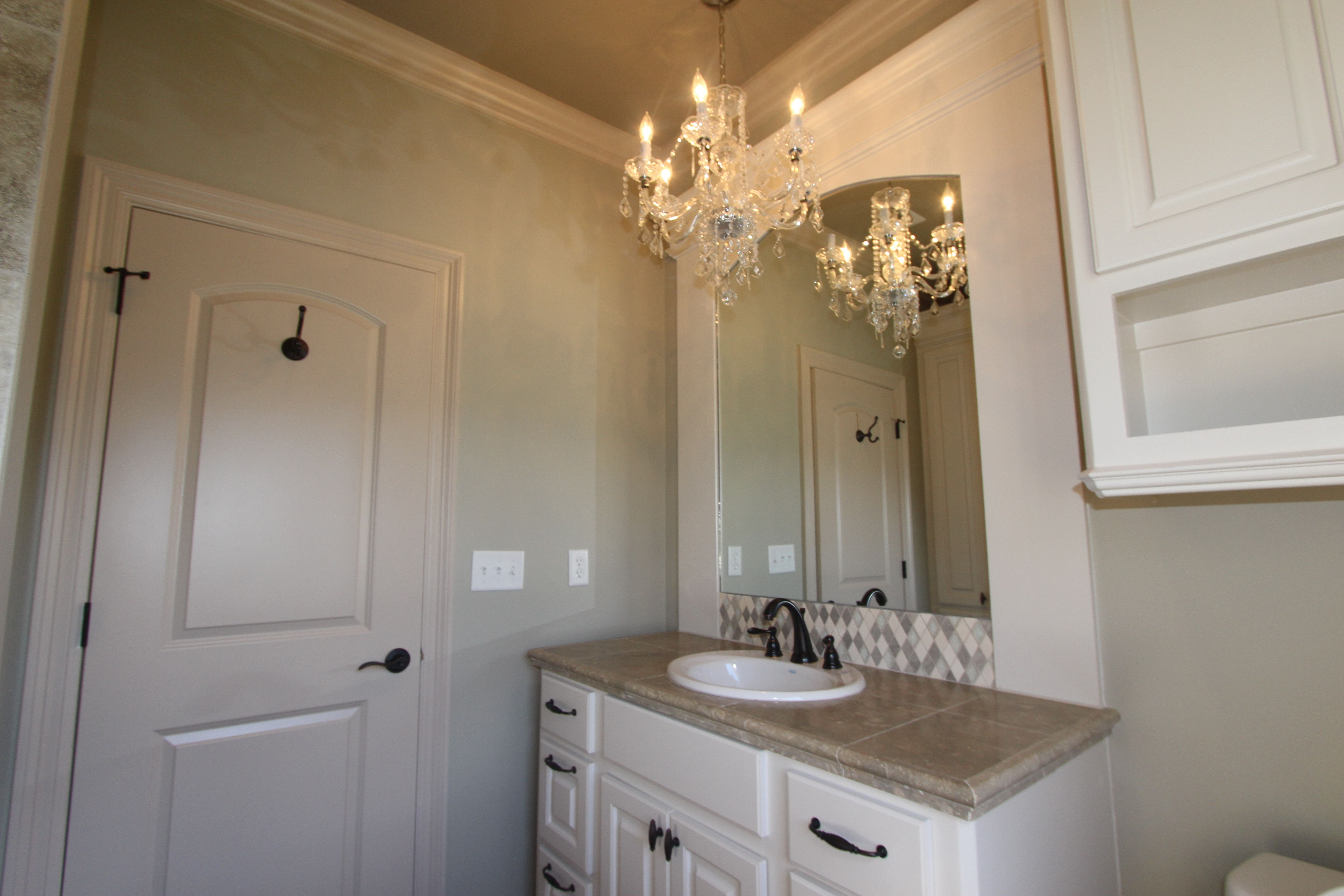 Elegant guest bath with custom vanity, custom tile detail, and chandelier.
