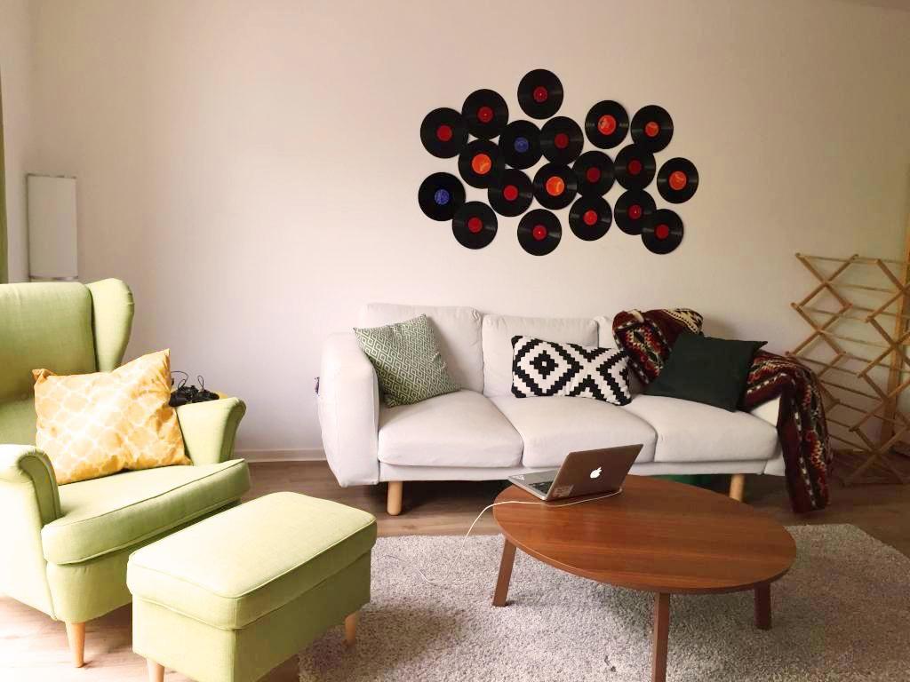 gemütliches wohnzimmer mit wanddeko aus alten schallplatten