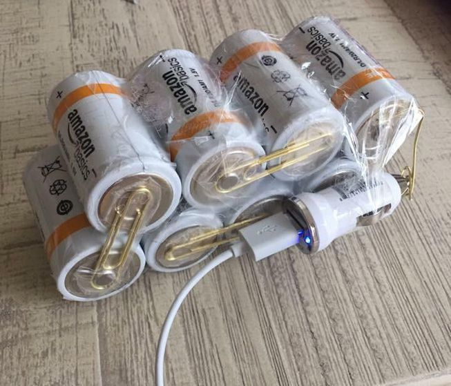 D batteries paper clipped and taped together to charge a cellphone