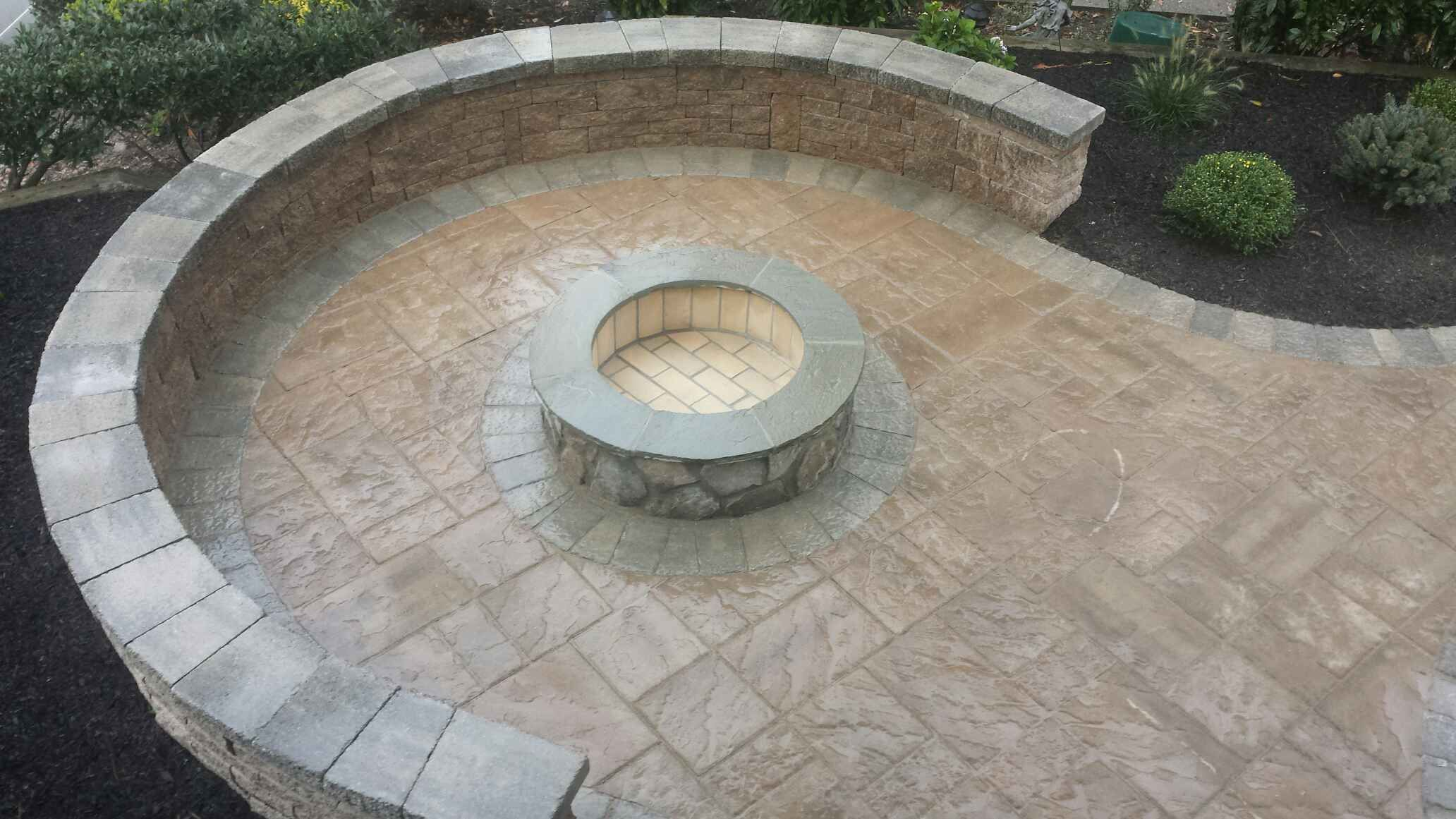 outdoor stone firepit with paver patio and sitting wall built by