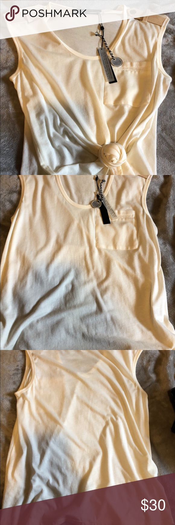 Andrew Marc Sleeveless Shirt/ Leather straps Really cute Andrew Marc sleeveless cream colored shirt with leather shoulder straps! I bought it from a boutique here in town and just haven't worn it as creams and whites aren't usually my colors🤭 It's a shame it's just sitting in my closet! As I was taking the pictures I noticed a couple tiny spots on the left side hem area, and being that they weren't there before, and I've never worn the shirt, I'm thinking they'll probably come out in the…