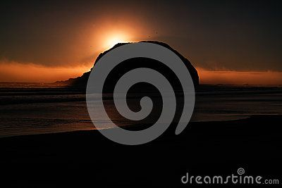 A sunset behind a large rock on the Oregon coast.