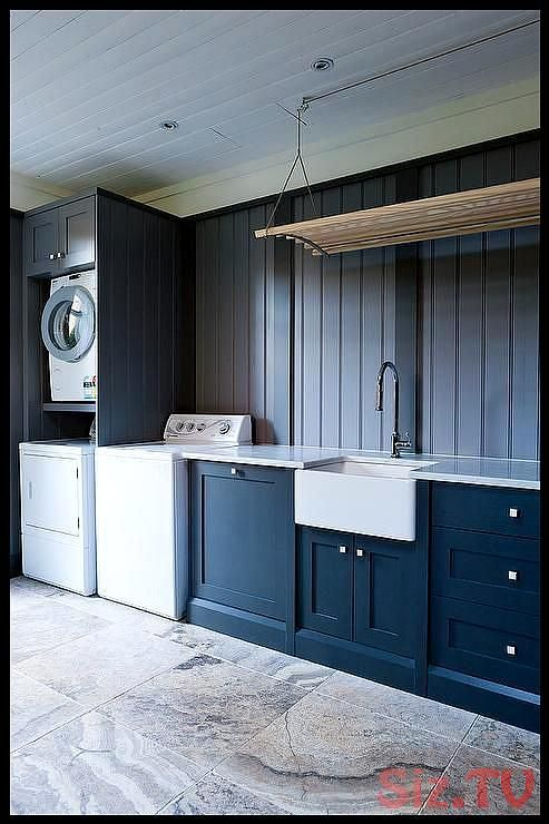 Well appointed blue laundry room features a wood and rope pull down drying rack