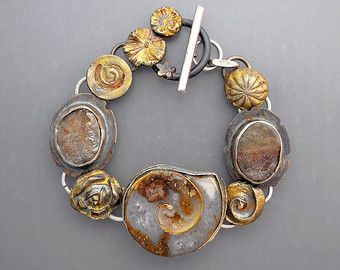 A sterling silver bracelet with natural hessonite garnet crystals, pastel ocean jasper cabochons and silver elements. The clasp is embellished with a tiny